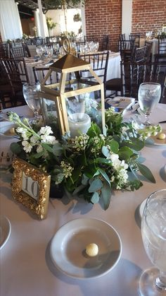 Gold lantern centerpiece with greenery at base.