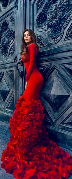 Victorian red fitted dress with ruffles thighs down and trail. Dramatic evening look, the fitted dress accentuates the female body and thick ruffles giving an exotic effect. The Victorian red is eye-catching as it gives an exciting mood.