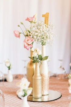 Gold bottle centerpiece and table number with roses and baby's breath - gold wedding ideas and inspiration - diy wedding centerpieces using wine bottles Wedding Centerpieces Mason Jars, Floral Centerpieces, Wedding Decorations, Centerpiece Ideas, Rose Gold Centerpiece, Mirror Centerpiece, Wedding Bottles, Centrepieces, Decor Wedding