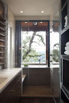 En suite bath to master bedroom; shelves surround a double sided fireplace; jacuzzi tub is outdoors, Marin home; interior by Erin Martin