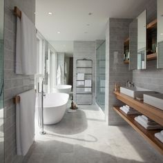 An open bathroom incorporating two countertop basins, minimalist disc operated taps, and a dramatic freestanding cast resin bath and tap with views stretching to Canary Wharf. A separate WC links to the bathroom, both of which are set against marble tiled floors and walls.