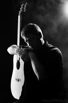 Low-key photography, portrait by studio light. Man with guitar.