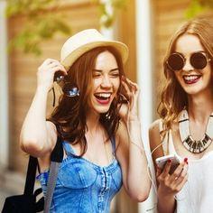 Primer plano de amigas riendo y escuchando música