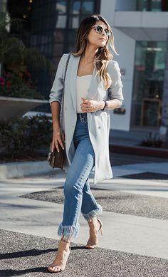 Street style look com blazer cinza, calça jeans e sandália bege.
