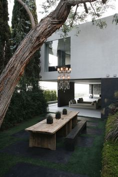 outdoor dining table and chandelier --  Concrete and glass home immersed on a cliff