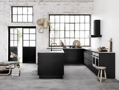black kitchen, no upper cabinets. Black framed windows and inside industrial space.