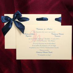Invitatia are fundalul crem iar culoarea textului este albastra. Aceasta intra intr-un suport din acelasi material crem, accesorizat cu o fundita din material textil de culoare albastra. #invitatie de #nunta #albastra