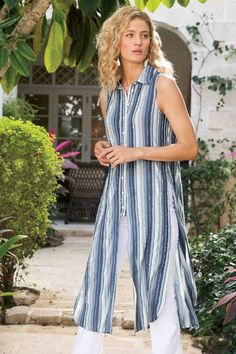 "This novelty striped jersey-knit tunic with its longer-length cardigan silhouette transitions from day to night with ease. Sleek detailing includes edge stitching along the classic collar, a mid-reaching center placket with buttons and rounded high-low hem. Blue/white. Rayon/poly. Misses 48""/50"" long. Indigo Stripes Tunic #2AH59"