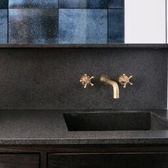 madeamano.com  Nuda Lava bathroom counter and splash back, Ossido blue wall tiles and a classic brass tap from Toni.dk