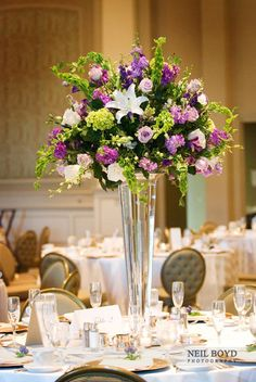 Tall table centerpiece with purple and white flowers