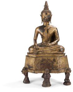 LAOS - XVIIe/XVIIIe siècle Statuette de bouddha en bronze laqué or, assis en dhyanasana sur une base portée par quatre lions, les mains en bhumisparsa mudra (geste de la prise de la terre à témoin). (Usures). Hauteur : 47 cm