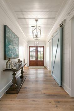 coastal foyer with blue sliding barn door   Mahshie Custom Homes