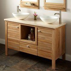 une commode en bois et deux vasques blancs dans la salle de bains