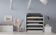 A white desk showing clean desk ideas like a letter tray for papers and tablets, boxes for storage and cord control and a glass vase for pens Maximize Space, Create Space, Clean Desk, Letter Tray, Ideas Para Organizar, Desk Shelves, White Desks, Study Space, The Way Home