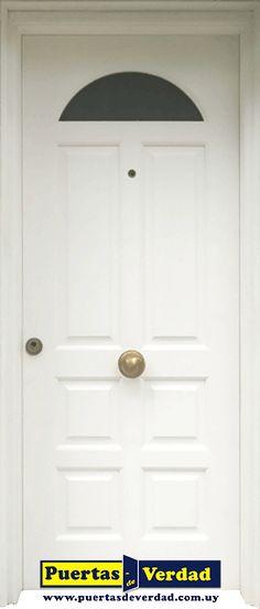 """Puerta exterior de madera maciza en 2"""" de espesor espigada y acuñada de borde a borde con replanes, cerradura de seguridad con multi anclaje, laqueada en blanco semi mate."""