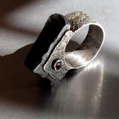 Rybka+Rybka+s+hlavou+přetěžkou,+železnou,+s+očkama+krví+podlitýma,+zkrátka+kumpán+do+nepohody.+Prsten+je+leptaný+a+patinovaný,+železo+v+hlavě+pronýtované+skrznaskrz.+Očka+-+surový+český+granát+-+pyrop,+jen+přeleštěný.+Železo+je+voskované+a+leštěné,+časem+ale+může+trošku+přireznout,+což+není+na+škodu.+Vzhledem+k+tvaru+a+váze+hlavy+prstenu+by+prsten+neměl+na...