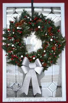 Simple Christmas Door Wreath created with an evergreen base with added berries and bow from A Pretty Life in the Suburbs.