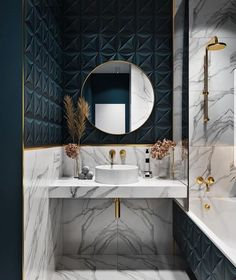 Cool grey marble and teal geometric tiles, gold elements and a round mirror for a luxurious and glam bathroom.