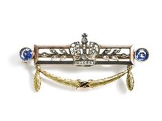 A Fabergé diamond and sapphire brooch, adorned with the Russian mitre crown and stylized leaves, set with rose-cuts diamonds, flanked by two circular-cut sapphires, beneath a garland with ribbon, mounted in two-coloured 14k gold and silver. Workmaster August Hollming, St. Petersburg, 1908–1917.