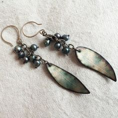 Dressy. Dramatic. Playful.  Real leaves were used to texture the copper for these enamel earrings.  After applying the texture, cutting them out and shaping them to look more natural, I fired transparent vitreous enamel on both sides.  I over-fired this pair intentionally, to get the lovely colors. I added fresh water cultured pearl berries in peacock and purple shades. Sterling silver wire and chain was oxidized. Length is 3.25 from top of wire.  Shipped in an eco-friendly gift box.  Thanks…