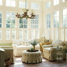 Wood shutters (installed on the lower portions of the tall windows) add light-filtering privacy in the sunroom. visually reducing the room's volume without sacrificing the views that connect the sunroom to the surrounding landscape. Sunroom Windows, Tall Windows, Sunroom Window Treatments, My Living Room, Living Spaces, Floating Shelves Kitchen, Sunroom Decorating, Wood Shutters, Cafe Shutters