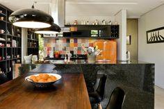un îlot en granit noir et un dosseret en carreaux multicolores dans la cuisine