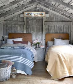 Guest Cottage Bedroom. The poplar 1940s headboards are painted with floral detail, and the linens are Home Goods bargains.   An old metal washtub works as a nightstand.  photo: Christopher Baker