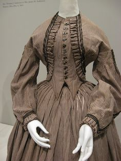 Linsey-wooley striped day dress with black braid (to imitate a bolero) (American), circa 1862.
