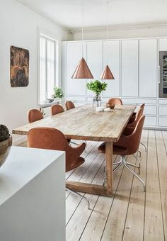 Bright dining room featuring a large wooden plank table, brown leather dining chairs and pendants in copper.