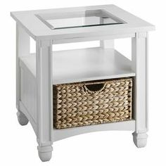 """Glass-top end table in white with column-inspired legs and a woven seagrass basket.   Product: End tableConstruction Material: Wood, sea grass and glassColor: Cottage whiteFeatures: One shelfWoven basket includedDimensions: 25"""" H x 23"""" W x 23"""" D"""