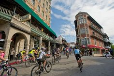 bikers riding past the Basin Park Hotel before the Fat Tire Festival in downtown Eureka Springs, Arkansas.