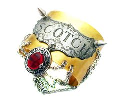 """An undenaibly badass steampunk/punk rock cuff featuring a vintage lead free pewter decanter label outfitted with 2 small steel spikes, and a large blood red neo victorian amulet.    Also features an abundance of stainless steel chain, and a wow factor that cannot be measured ; )    Cuff width- 2 inches    The brass portion of the cuff is made from pure brass, and will aquire a natural patina over time. Please be sure not to adjust your cuff too much, as this will cause """"metal fatigue""""…"""