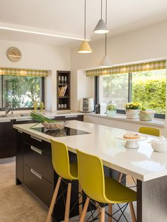 A kitchen and an island table, in whites, blacks and yellows. By Liat Hadas, Architecture & Design.