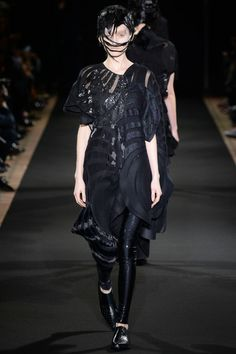 Black deconstructed dress with geometric patterns paired with shiny black leggings by Junya Watanabe. #IStyleNY #Style