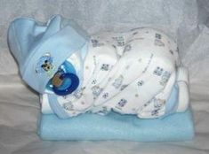 Diaper Baby - made out of rolled up diapers, a baby blanket, baby hat, pacifier and a baby Onesie. Go to Youtube and type in: How to make a diaper baby - Sleeping Baby Girl (Diaper Cake) by sue.ransongrant