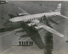 1950s Crew and customers line up on the ramp next to a Pan Am DC6 Clippe