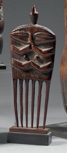 Peigne Hungaan - République Démocratique du Congo Bois H.: 20 cm - Belle patine brillante représentant un personnage sculpté traité schématiquement (tête, bras, seins, jambes). L'arrière est gravé de… - Eve - 08/12/2014