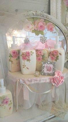 pink roses cover dainty bottles in front of lovely antique mirror.
