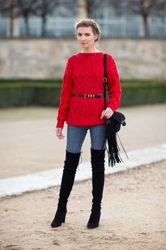 Red cabled sweater with black belt, jeans, thigh high boots, handbag with fringes. Paris Fashion Week, Street style.