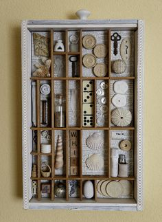 This is a found object assemblage done within an 10.5 X 17 old vintage drawer. I took the center of an old type tray and mounted it within the drawer. I whitewashed the wood and added a border of vintage looking trim. The found objects are all shades of white. The vintage items I