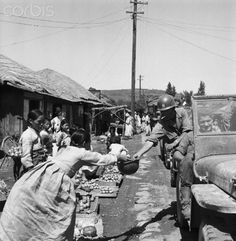 Reinforcements of American and South Korean troops are given apples as they pass through a village. 1950