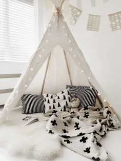 Bedroom / kids room / playroom - all white - teepee / tipi - white floor - texture / pattern - pillows - blanket / duvet - rug - light / fairy lights - bunting