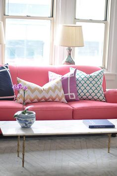 A bright couch with a stacked cushions can really add a unique element to your living room - especially in an apartment.