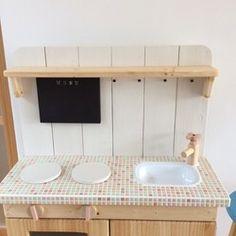 1センチのモザイクタイルを天板に使用したおままごとキッチンです。 蛇口のハンドルやコンロのつまみは、手で回すことが出来ます。お子様のおもちゃですが、お部屋のインテリアにもなります。 幅は26㎝と薄いのでお部屋にすっきりとおさまります。 シンクの部分は、ホーローを使っています。 黒板も付いているので、アイディア次第で、お子様の遊びも広がります。 コンロは、両面テープで固定しているので、不要になった際は、 取り外してフラットにお使い頂けます。*チョーク付き*黒板は緑・黒から選択できます*飾りのコップや計量スプーンは商品に含まれません*売り切れの際、同じ商品をおつくり出来ますので納期等お問い合わせください size:W54*D26*H76.5(天板までH46.5)