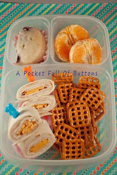 Easy Lunch Box lunch: turkey and cheese roll ups, pretzels, oranges and a homemade blueberry glazed doughnut muffin.