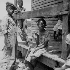 A group of African American migrant children sitting on the porch of a house on the Bayou Bourbeau plantation, Natchitoches, Louisianna, 1940.