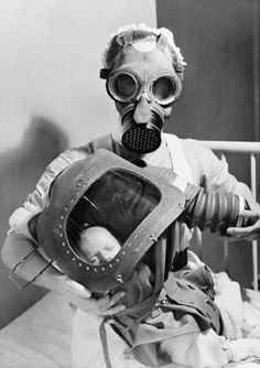 The Second World War: Nurse fitting a baby with its respirator (note the bellows arrangement). #history #worldwartwo (she is wearing a childrens micky mouse gas mask, she must have had a small head)