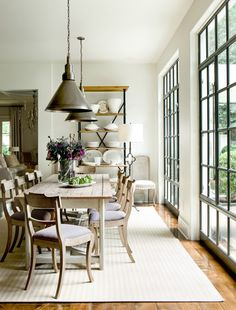 Beautiful dining space with full length windows, farmhouse dinning table and industrial pendant.  Natural elements of metal, wood and linen Interview With Suzanne Kasler | House & Home
