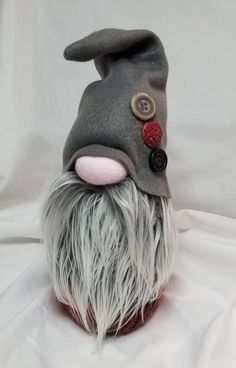 The silver bearded Asvald and his buttoned hat are sure to melt your heart! Asvald stands 10 inches tall and is hand made with all new materials including wool, fleece,felt, faux fur, button trim, polyester fiberfill, rice for a weighted base and of course love! Every gnome is named,