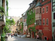 Riquewihr: High street (Général-de-Gaulle street): residence with an oriel window, colourful houses decorated with flowers and creepers, cafe terraces - France-Voyage.com